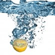 Fresh lemon dropped into water with bubbles — Stock Photo