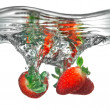 Fresh strawberry dropped into water with splash — ストック写真