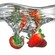 Fresh strawberry dropped into water with splash — Stock Photo
