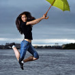 Girl jumping against sky and water with umbrella — Stock Photo