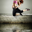 Girl jumping on the roof — Stock fotografie