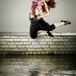 Girl jumping on the roof - Stock Photo