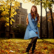 Woman in blue jaket posing in autumn park - Foto Stock