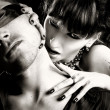 Vampire woman bites a blind man - Stockfoto