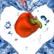 Red pepper with shape of heart from blue water isolated on white — Stock Photo