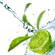 Foto Stock: Water drops on lime with green leaves isolated on white