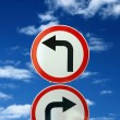 Foto de Stock  : Two opposite road signs against blue sky and clouds