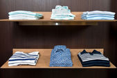 Wooden store shelf with color clothes — Stock Photo