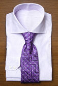 Shirt with violet tie on wooden shelf — Stock Photo