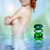 美丽的年轻女子在水与程式化的 spa 的石头 — 图库照片