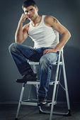 Attractive man in jeans sitting on stairs — Stock Photo