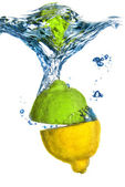 Lemon and lime dropped into water with bubbles isolated on white — Stock Photo