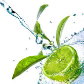 Water drops on lime with green leaves isolated on white — Stockfoto