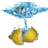 Lemon dropped into water with bubbles isolated on white — Stock Photo