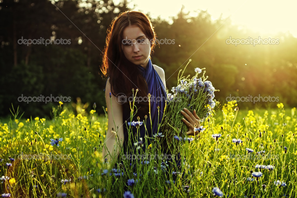 Girl gathering flowers on sunset — Stock Photo #3384700