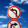 Two opposite road signs against blue sky and clouds - Stok fotoğraf