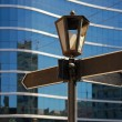 Blank signpost with ancient lamp against business building - Stockfoto