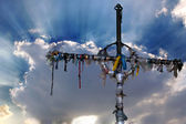 Cross with ribbons against clouds — Stock Photo