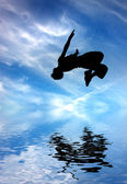 Silhouette of jumping man against blue sky and clouds — Stock Photo