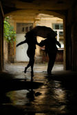 Silhouette of couple with umbrella running from rain — Stock Photo