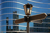 Blank signpost with ancient lamp against business building — ストック写真