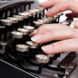 Royalty-Free Stock Photo: Fingers on vintage typing machine on white