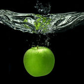 Green apple dropped into water with splash isolated on black — Stock Photo