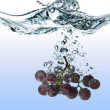 Blue grape dropped into water with splash isolated on white - Stok fotoğraf