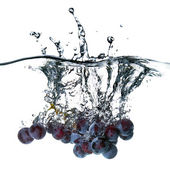 Blue grape dropped into water with splash isolated on white — Stock Photo