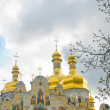 Laura in spring. Golden domes over cloudy sky — Stock Photo