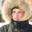 Man in warm jacket with furry hood — Stock Photo