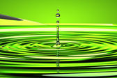 Water droplet and waves over green — Stock Photo