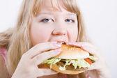 Fat girl with a hamburger — Stock Photo