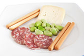 Fava beans, breadstick and salami — Stock Photo