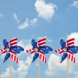 图库照片: Patriotic AmericPinwheels on Sunny Day Cloud Background.
