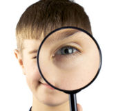 Kid using magnifying glass — Stock Photo