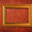 Gold frame on a red wall background — Stock Photo #3115184