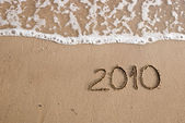 Year 2010 written on the sand — 图库照片