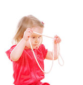 Little serious girl holds a pearl necklace — Stock Photo
