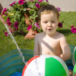 Toddler playing with water in the hot day — Stock Photo
