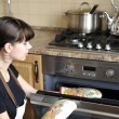 Beautiful housewife using the oven — Foto Stock