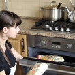 Beautiful housewife using the oven — Stockfoto