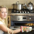 Stock Photo: Beautiful housewife switching oven