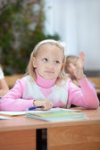 First grader girl puts her hand up — Stock Photo