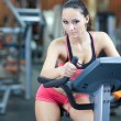 Girl  is cycling in fitness hall - 