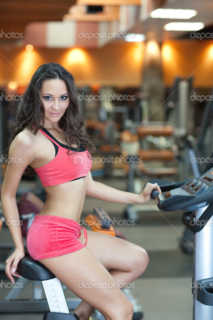 Sporty Girl in fitness hall is cycling — Stock Photo #3648807