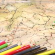 Foto Stock: Color pencils on old map