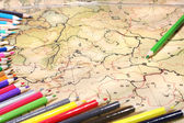 Color pencils on old map — Stock Photo