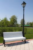 Bench under lamp in city park — Foto Stock