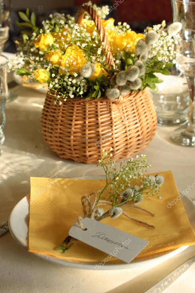 Festive table setting in yellow with a flower arrangement on the background  Stock Photo #2770622